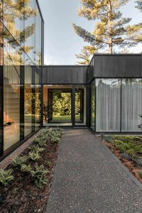 Residence de l'Isle by Chevalier Morales in Montreal, Quebec: Exterior view of midcentury modern structure with ceiling height glass windows, steel frames, and sliding doors