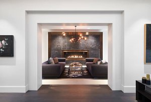 Annex Coach House in Toronto: Linear gas fireplace is inset into a dramatic wall of dark veined stone trimmed in bronze.