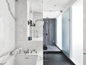 Annex Coach House in Toronto: The master bathroom is illuminated through a screen of alternating back-painted and acid-etched glass with diffuse natural light from the skylight at the stair. Inside, statuario marble and charcoal coloured porcelain tile create a dramatic contrast of light and dark.