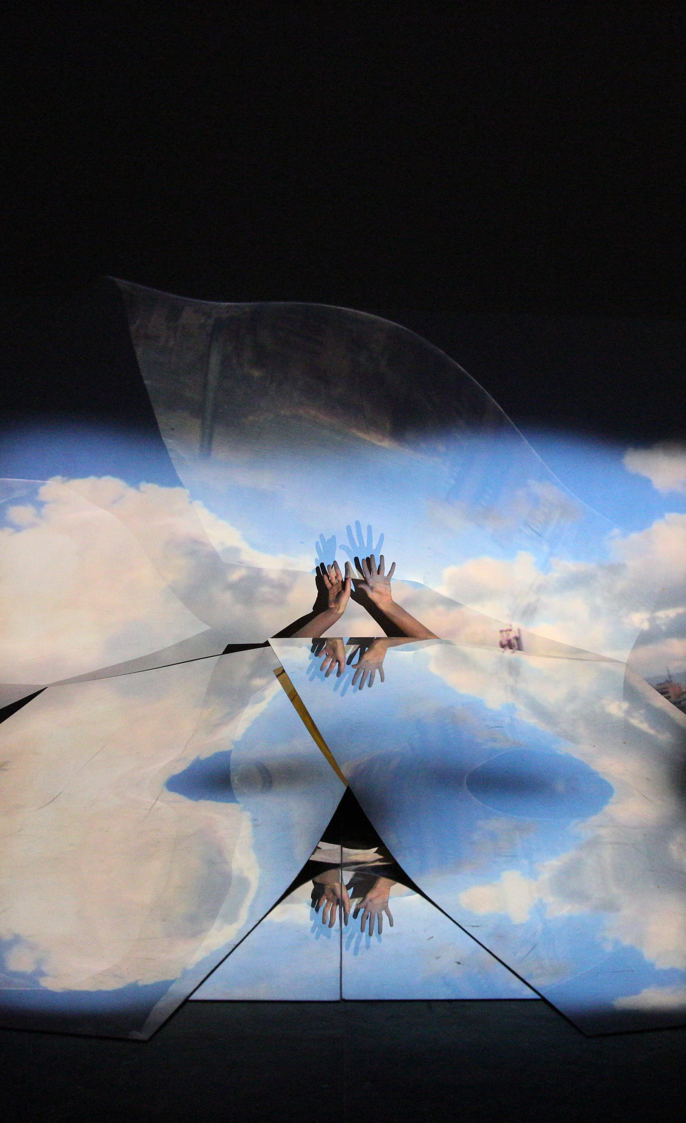 Two hands reach out behind set pieces painted with clouds