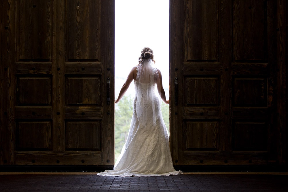 A bride standing in the doorway of the barn at her Stove Prairie Ranch wedding.