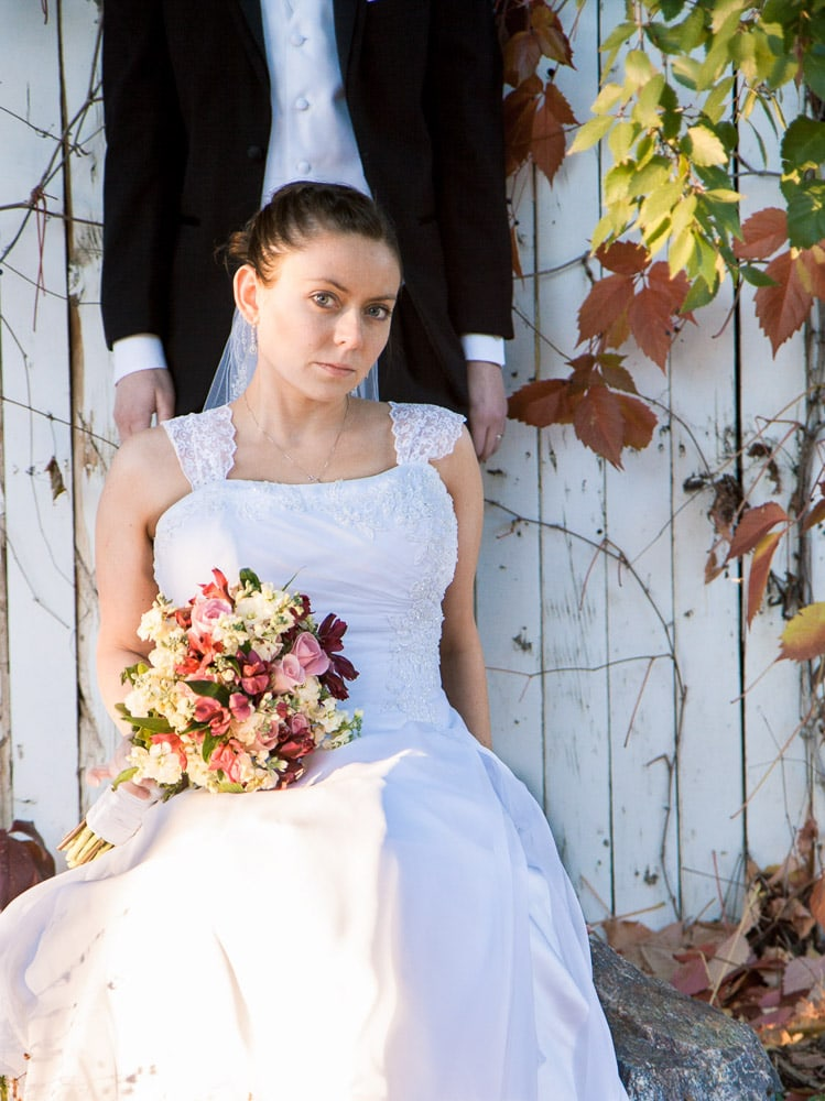 A bride sits near colorful leaves at her modern Lionsgate Event Center wedding.