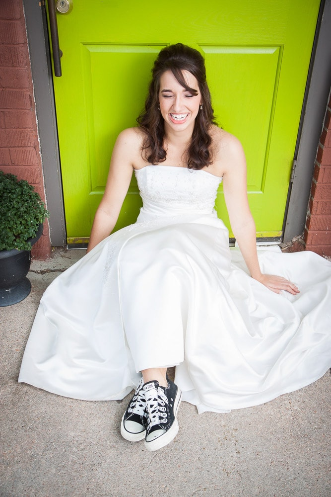 A modern bride smiling in her converse shoes as she sits in front of a bright green door in Fort Collins.