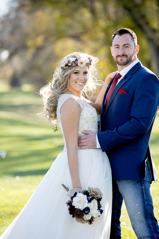 A bohemian Colorado bride and her new groom posing for their photos at their Greeley Country Club wedding.