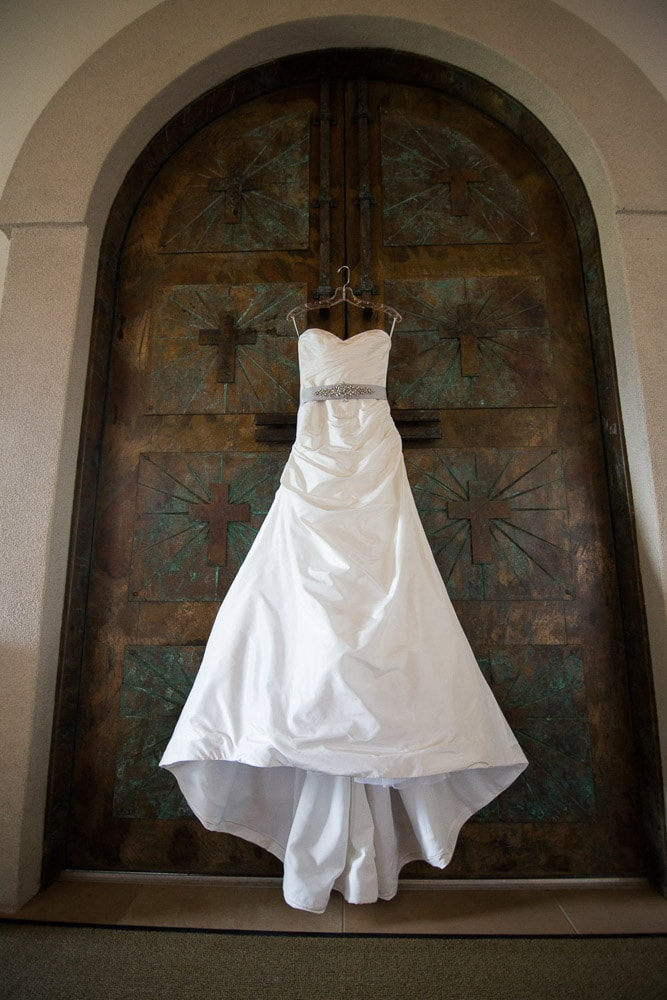 A wedding dress hanging on a rustic iron door at a modern Colorado mountain wedding.