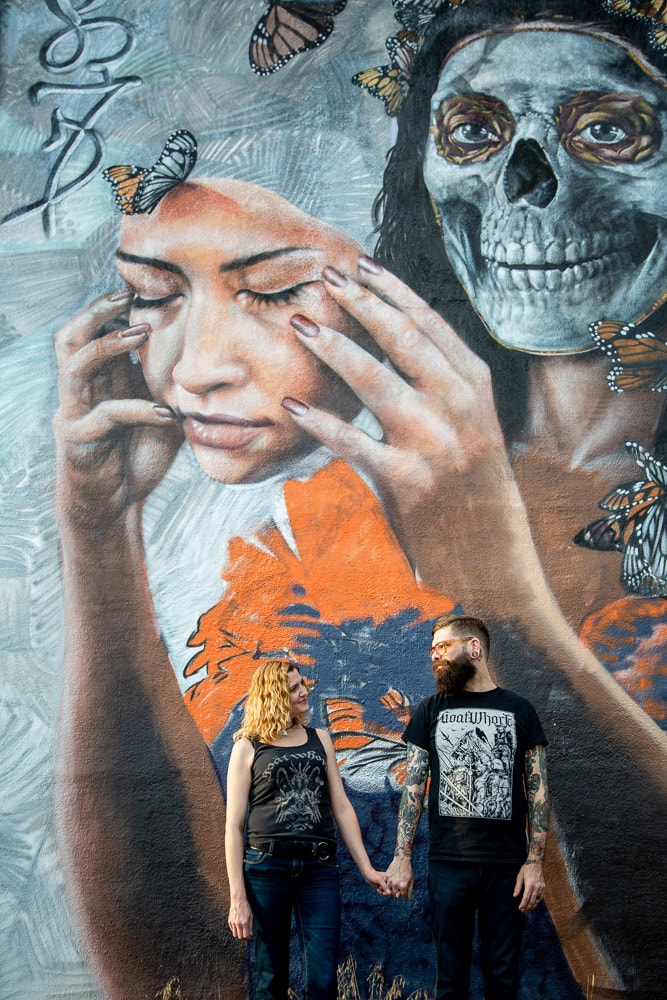 An engaged couple holds hands in front of a wall painted with artwork during their urban Denver engagement photo session.