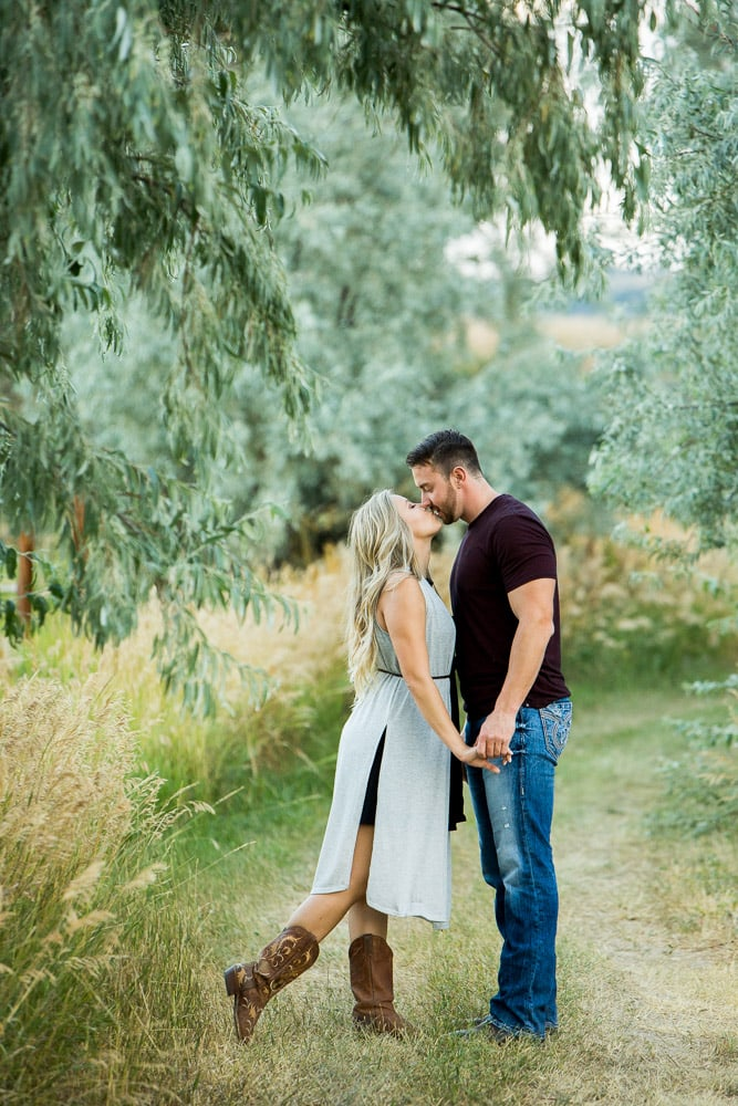 A young couple kiss under the hanging trees during their romantic outdoor engagement photo session in Fort Collins.