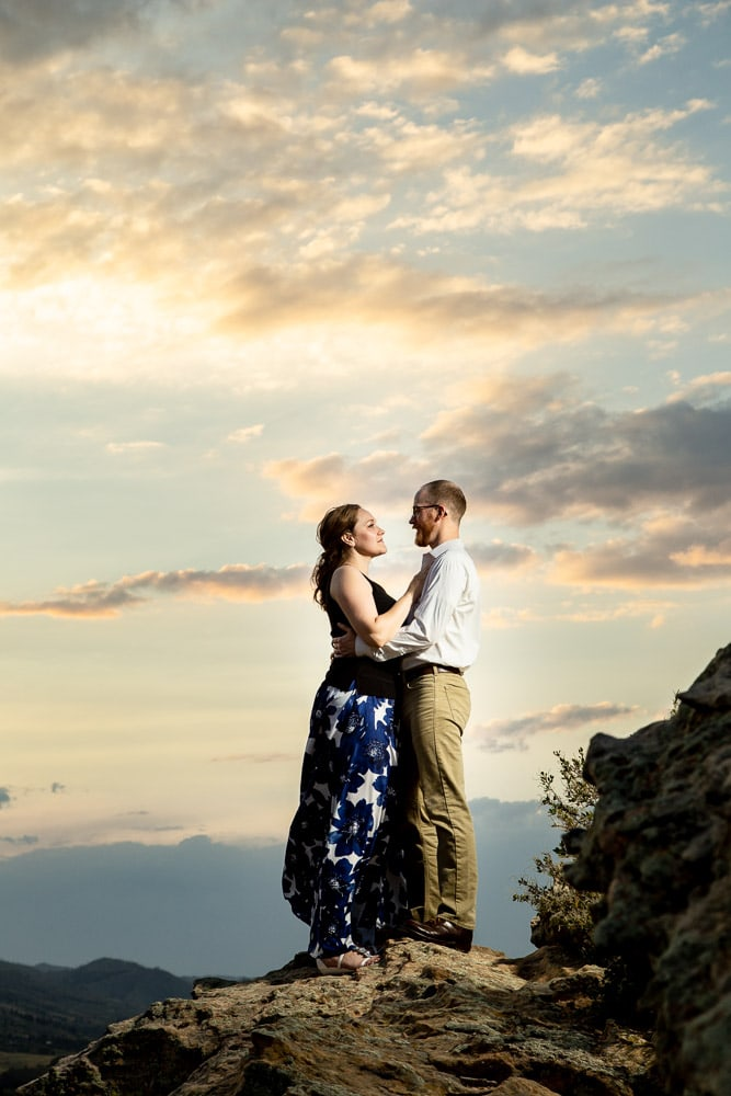 A couple hold each other on a rock formation at Horsetooth Reservoir during their sunset engagement photo session.