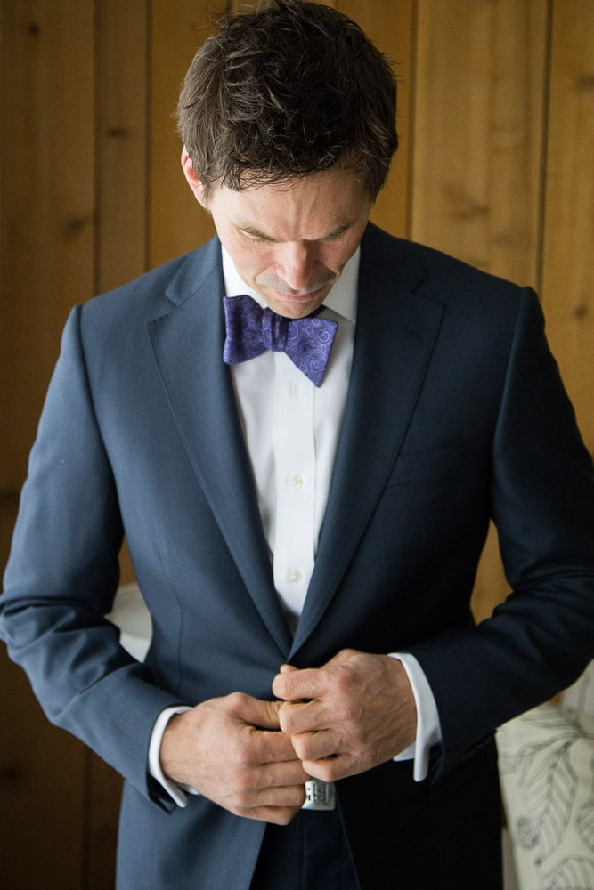 A stylish groom buttons his suit as he prepares for his modern Fort Collins wedding.