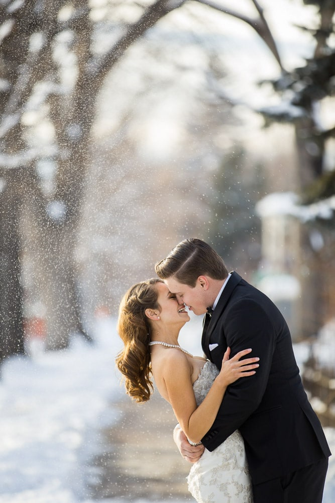 A Colorado bride and groom kiss under the falling snow at their vintage themed Fort Collins winter wedding.