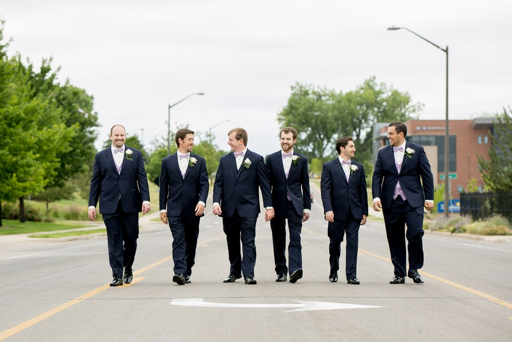 A groom and his groomsmen walk down the street laughing before a Fort Collins Hilton wedding.