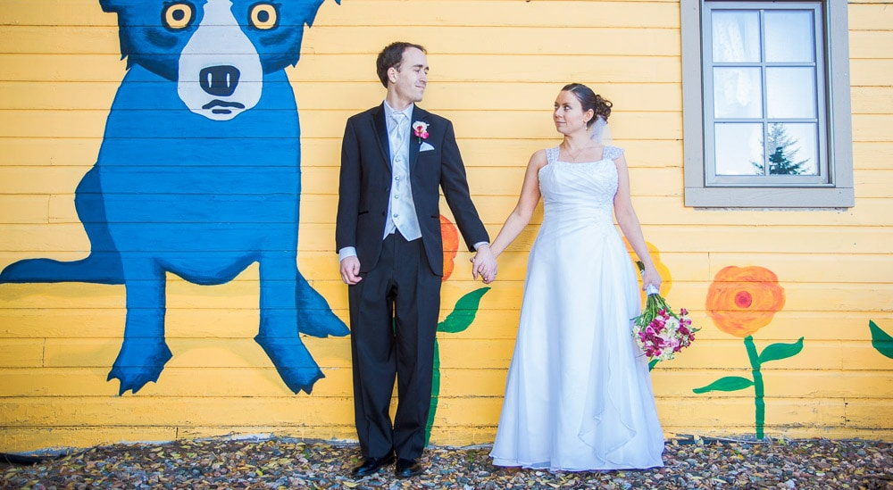 A bride and groom hold hands in front of a bright yellow wall at their modern wedding at the Lionsgate Event Center.