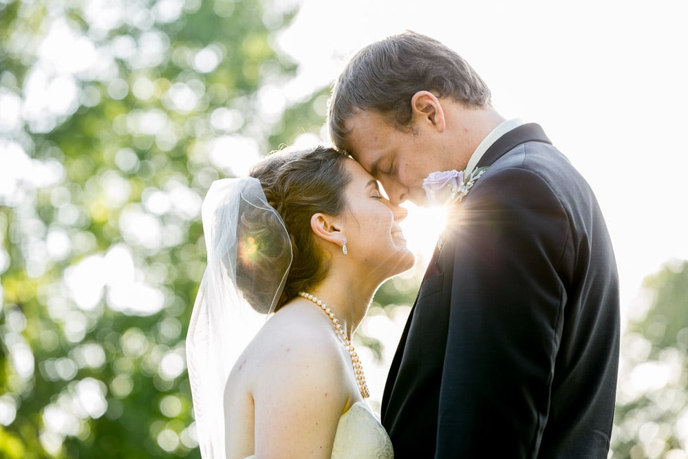 A bride and groom touching foreheads with the sun peaking through on their wedding day in Loveland, Colorado.