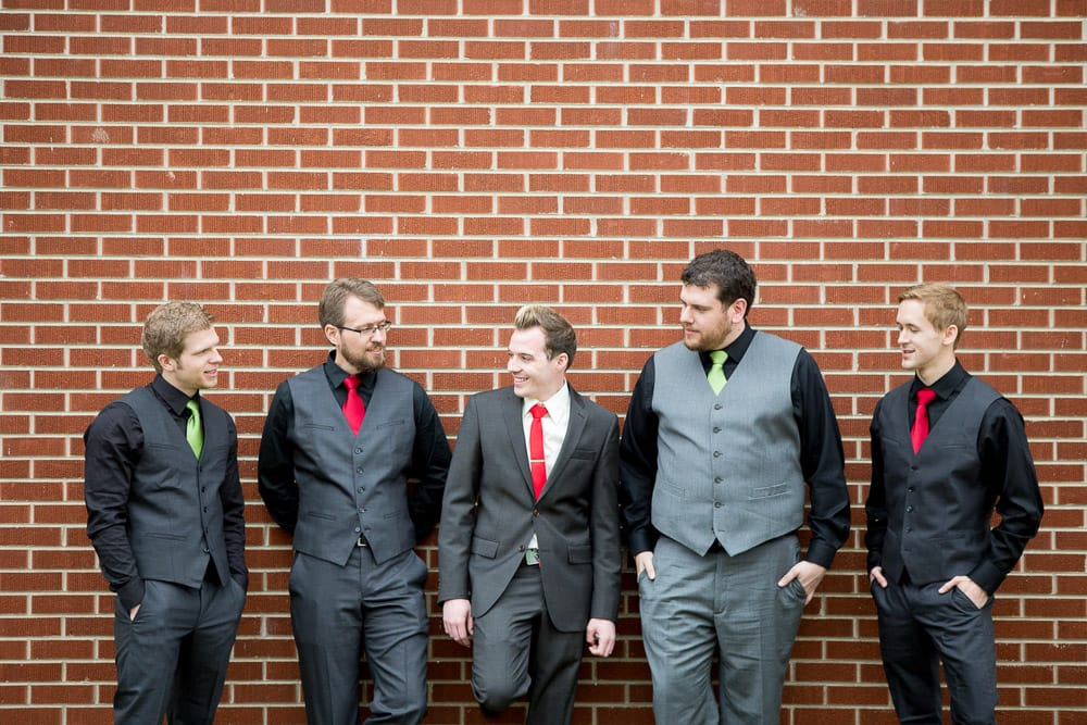 A groom and groomsmen leaning against a brick wall before his Loveland, Colorado wedding at the McCreery House.