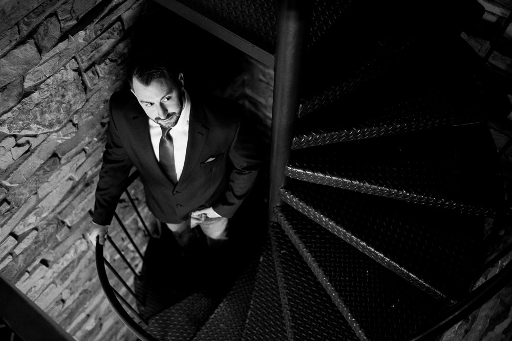 Black and white dramatic photo of a groom in spiral stairwell on his wedding day at the Greeley Country Club.
