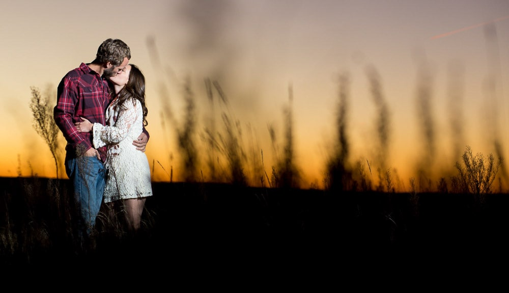 A couple kissing in a field of tall grass at sunset during their outdoor engagement photo session near Fort Collins.