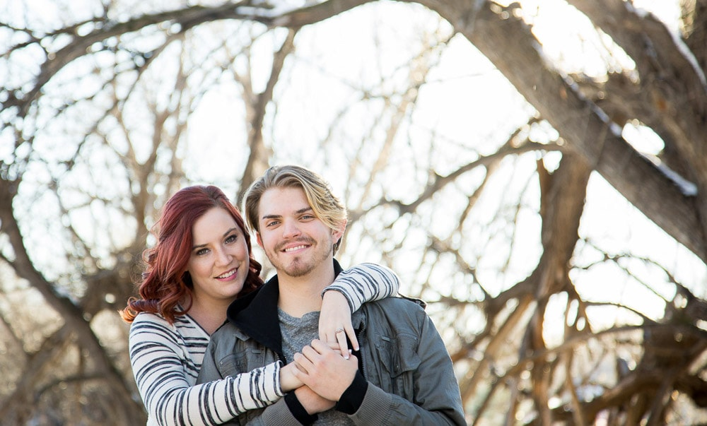 A young couple smile and hold eachother in a park durung their fun outdoor engagement photo session in Fort Collins.
