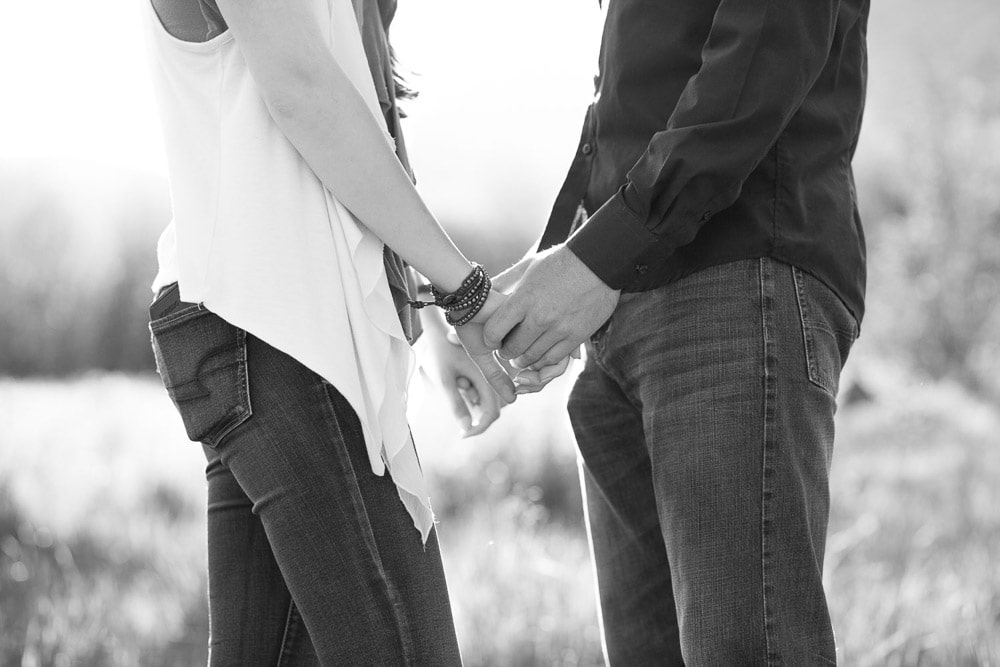 A couple holding hands in field.