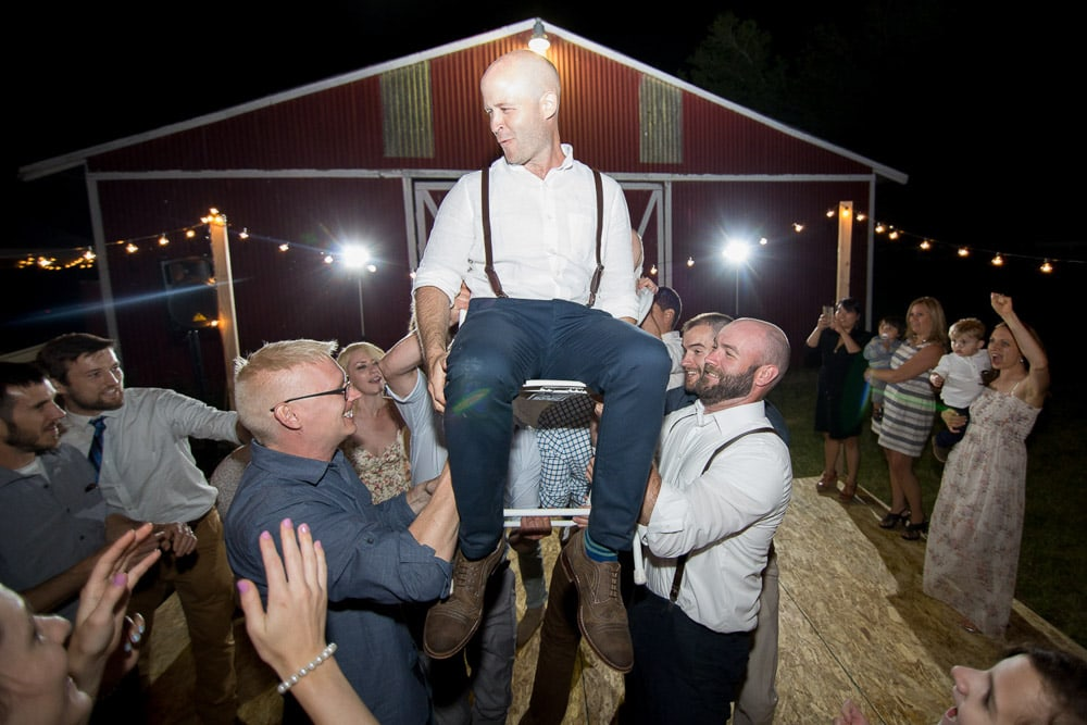 A groom being lifted up on a chair at his DIY barn wedding in Fort Collins, Colorado.