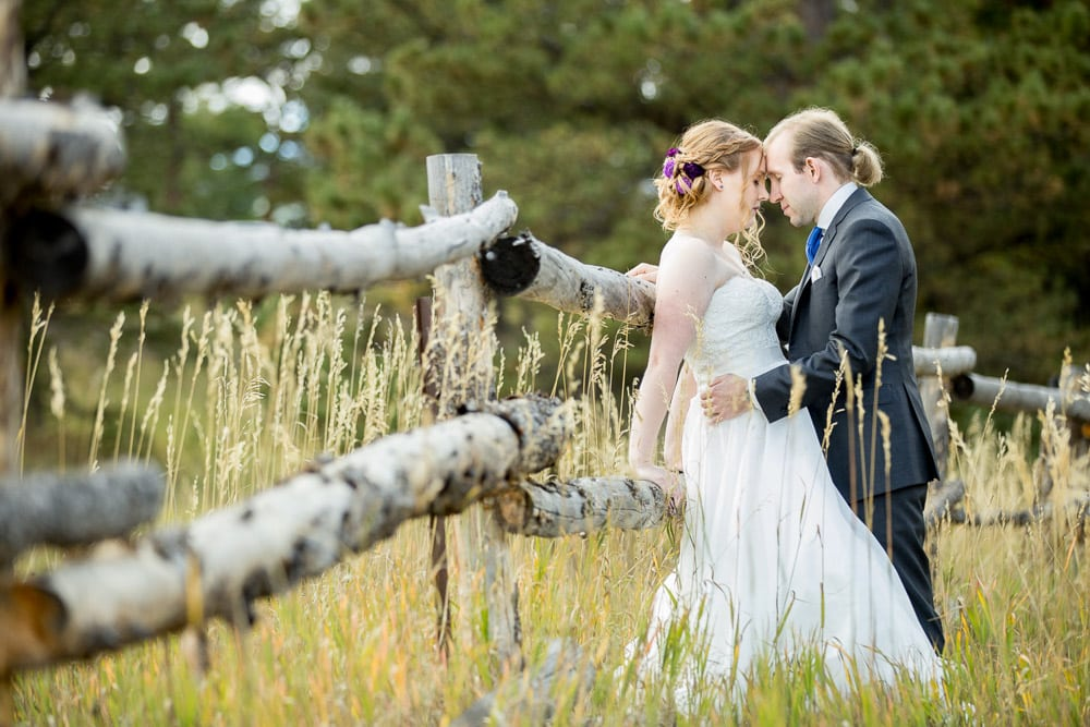 A bride and groom share a quiet moment leaning against a wooden fence in a field at their Wild Basin Lodge wedding.