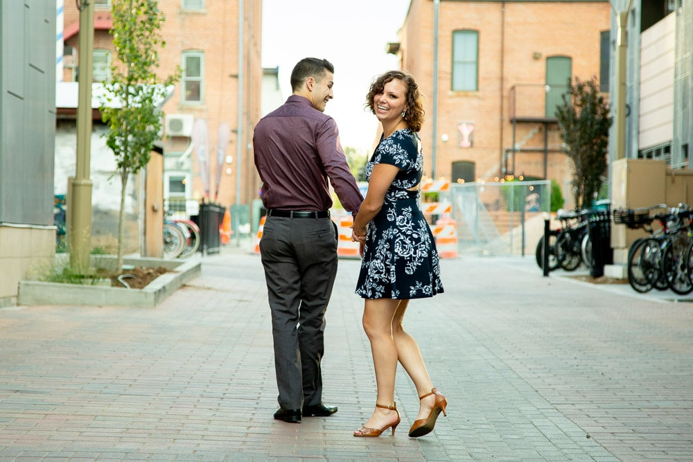 A girl looking back and smiling while holding her fiance's hand during their old town Fort Collins engagement photo session.