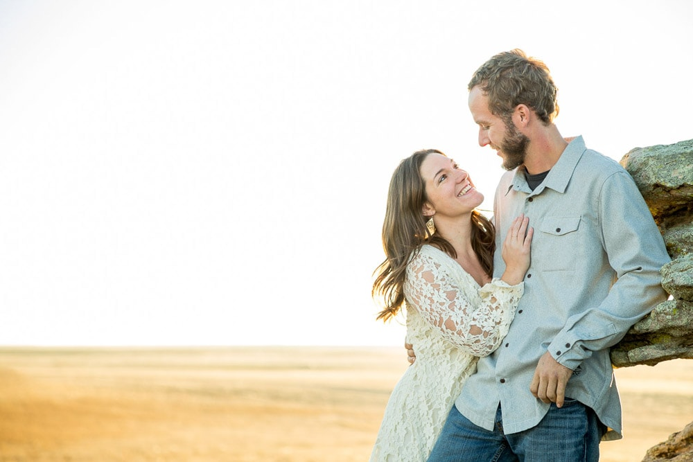 A couple smile at eachother during their outdoor engagement photo session near Fort Collins, Colorado.