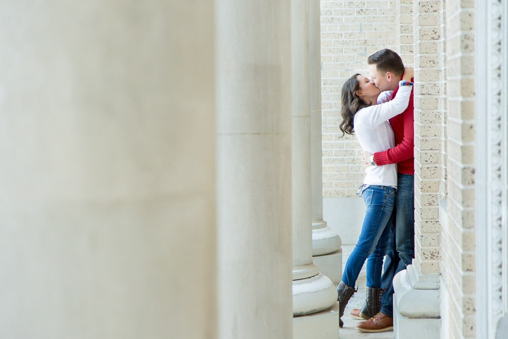A couple kissing near the CSU admin building during their winter engagement photo session in Fort Collins.