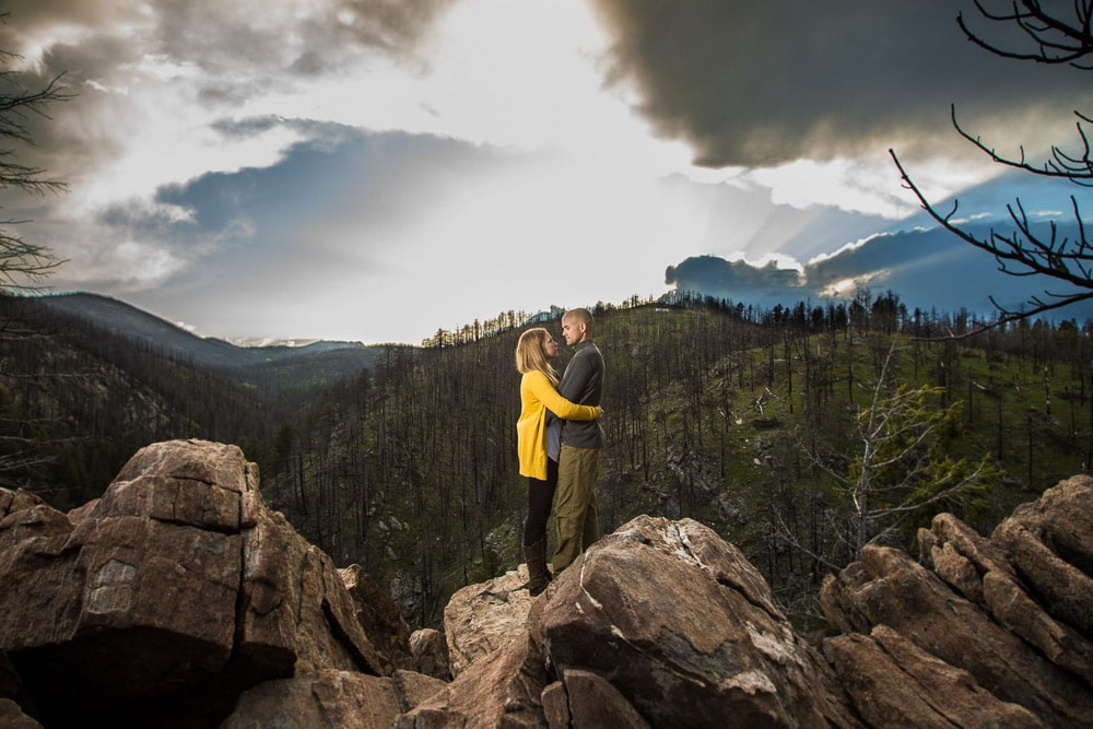 A couple stand on a cliff in the mountains during their outdoor engagement photo session in Fort Collins, Colorado.