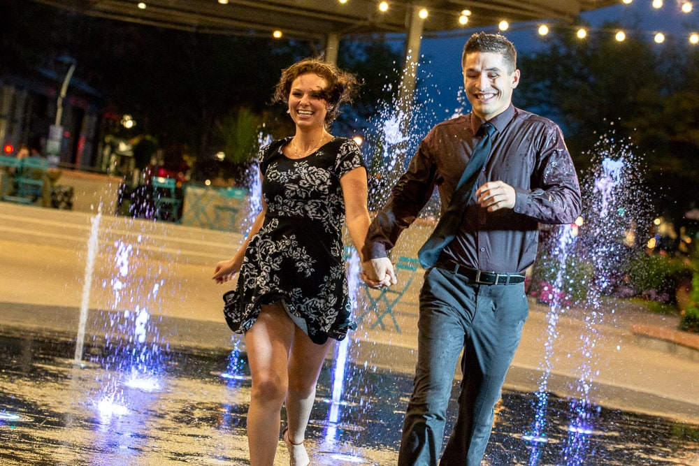 An engaged couple holds hands and runs through a fountain at night in Old Town Fort Collins.