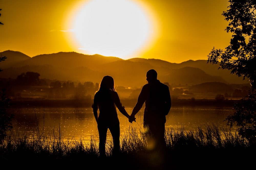 A couple hold hands at sunset in front of a lake during their Fort Collins engagement session.