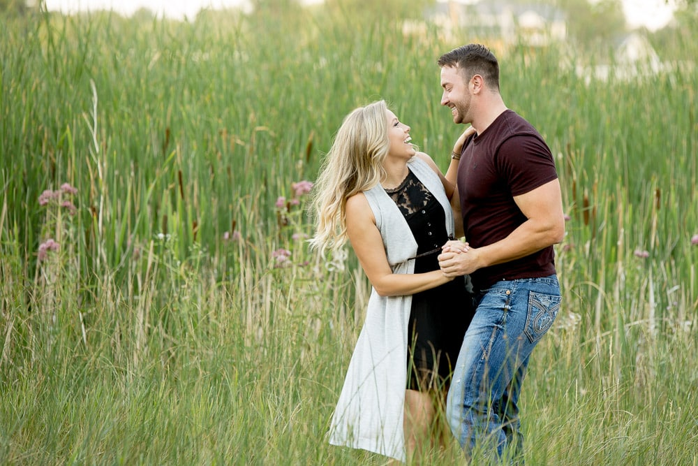 A couple dancing in field of tall grass during their romantic outdoor engagement photo session in Fort Collins.