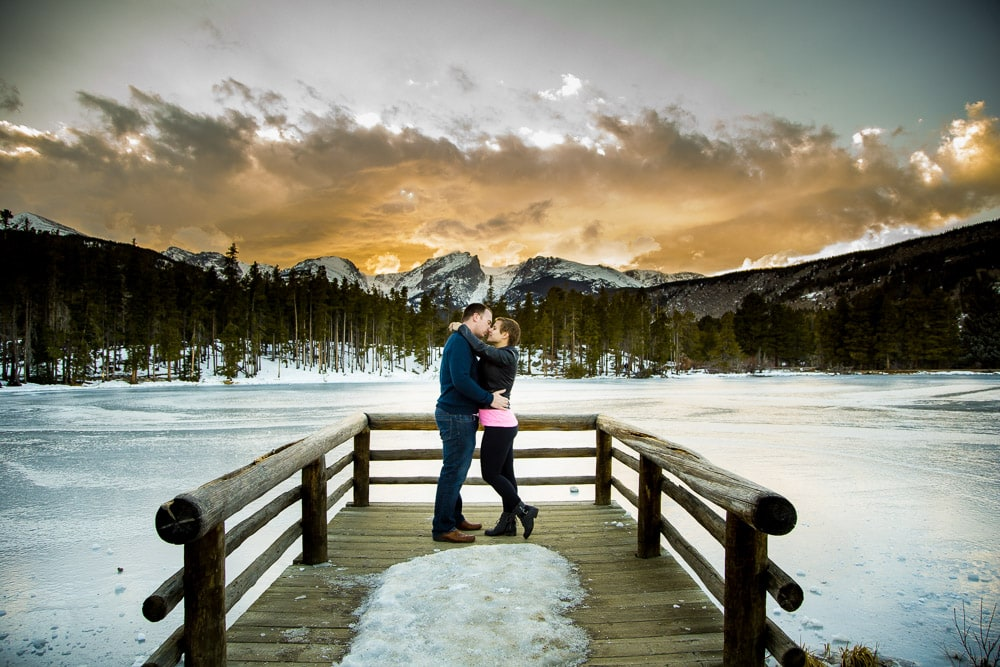 A couple standing ona pier in the snow during their Rocky Mountain National Park engagement photo session.