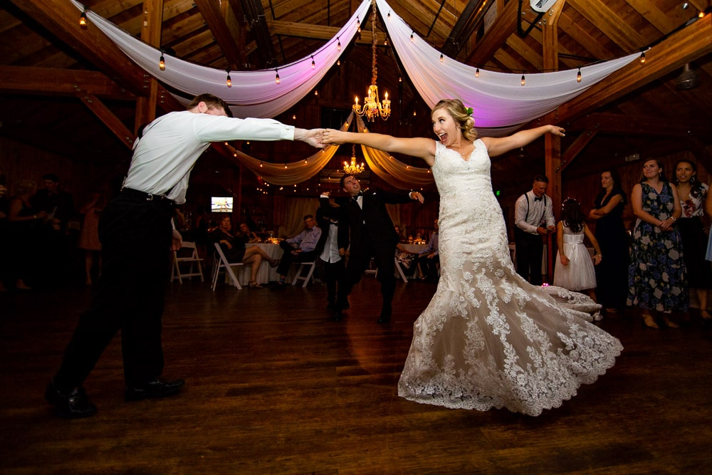 A bride dancing at her wedding reception at the big red barn at highland meadows in Windsor, Colorado.