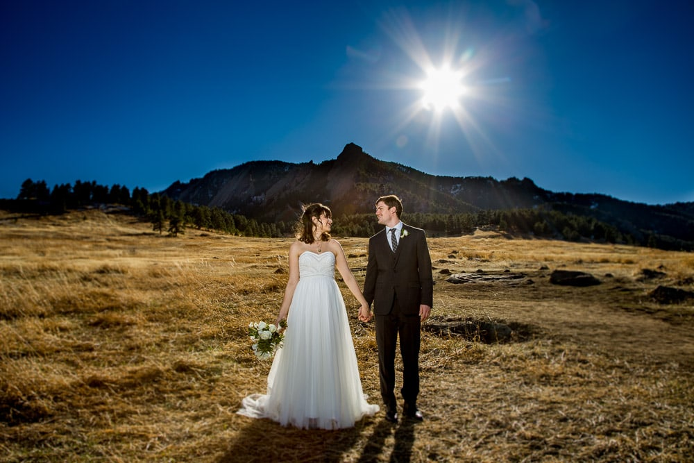 A modern bride and groom hold hands in a field with the sun blazing overhead after their Hotel Boulderado wedding.