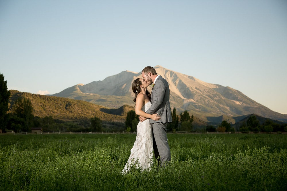 An outdoorsy bride and groom kiss oin a field in the mountains at thier ColoradoDIY wedding.