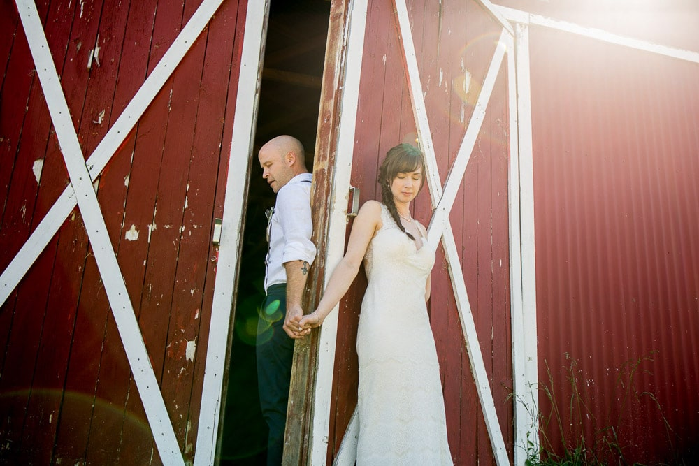 A bride and groom hold hands and pray by the barn door at thier DIY barn wedding in Fort Collins.