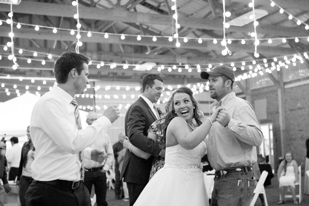 A bride laughs on the dance floor at her DIY barn wedding in Fort Collins.
