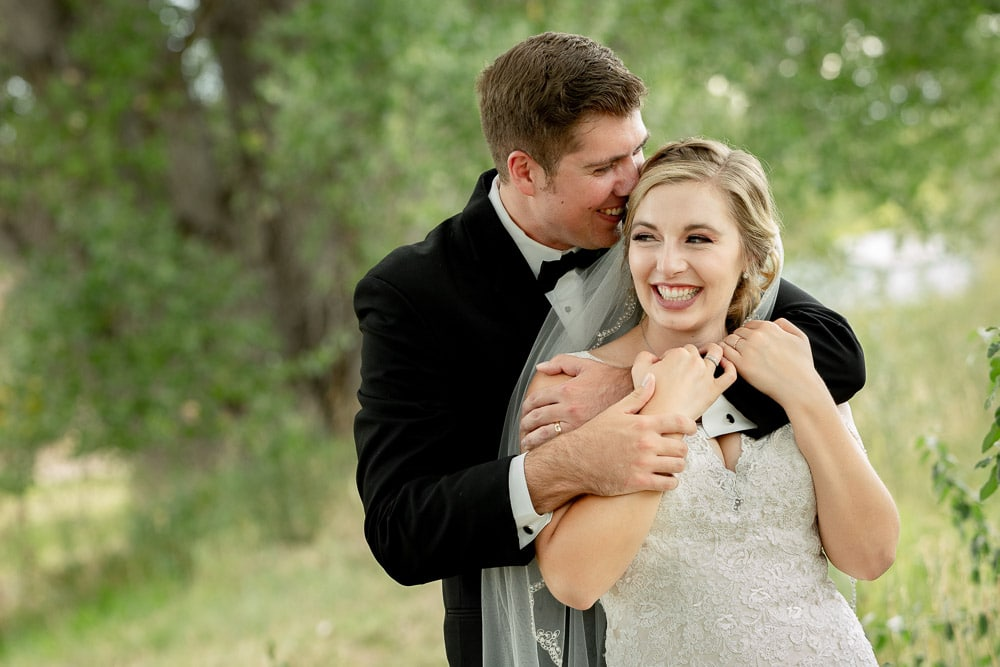 A groom whispers in his brides ear after their modern Fort Collins wedding.