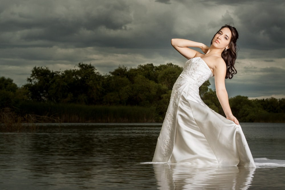 A bride standing in a lake in her wedding dress during her trash the dress photo session.