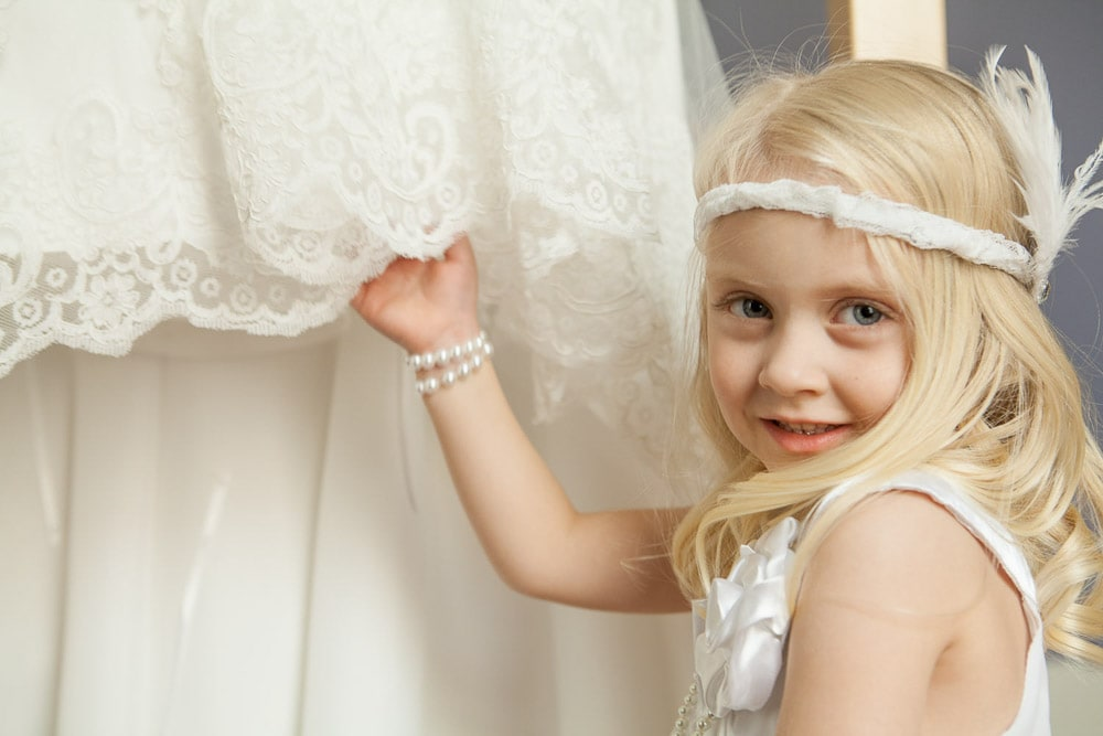 A flower girl in a vintage dress and headband stands near a wedding dress.