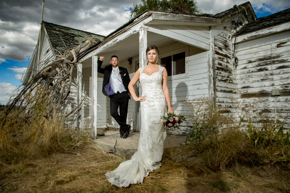 A modern bride and groom pose in front of an olkd rundown house before their Longmeadow Event Center wedding.