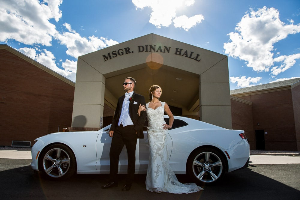 A stylish bride and groom pose with a sports car after their Modern COlorado wedding.