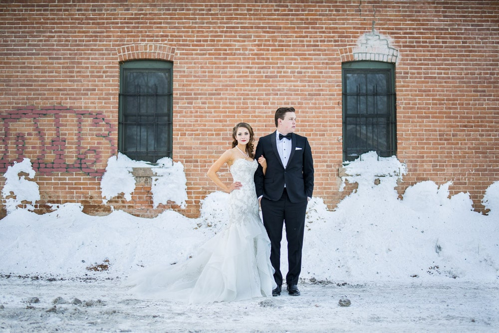 A stylish bride and groom stand in the snow by an old brick building on their Fort Collins winter wedding day.
