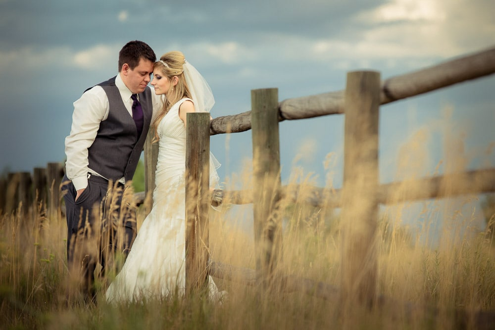A bride and groom lean against a fence in a field of tall grass on their wedding day in Loveland, Colorado.