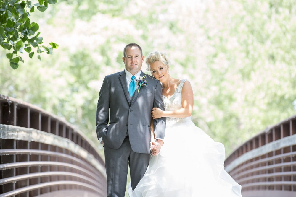 A modern bride and groom on a bridge at their Pelican Lakes Golf Course wedding in Windsor, Colorado.