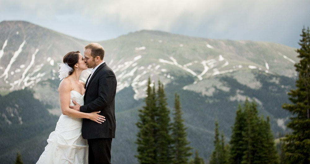 A bride and groom kissing atop the mountain at their Winter Park Resort wedding at Lunch Rock.