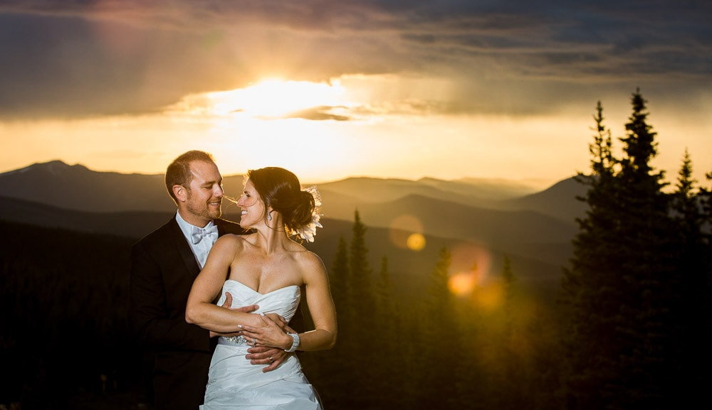 A bride and groom at sunset at the top of the mountains at their Winter Park Resort wedding.
