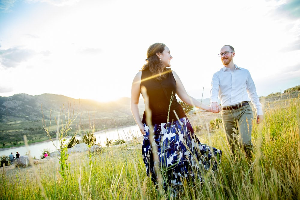 A girl walking through the tall grass holding her fiance's hand during their engagement photo session at Horsetooth Reservoir.
