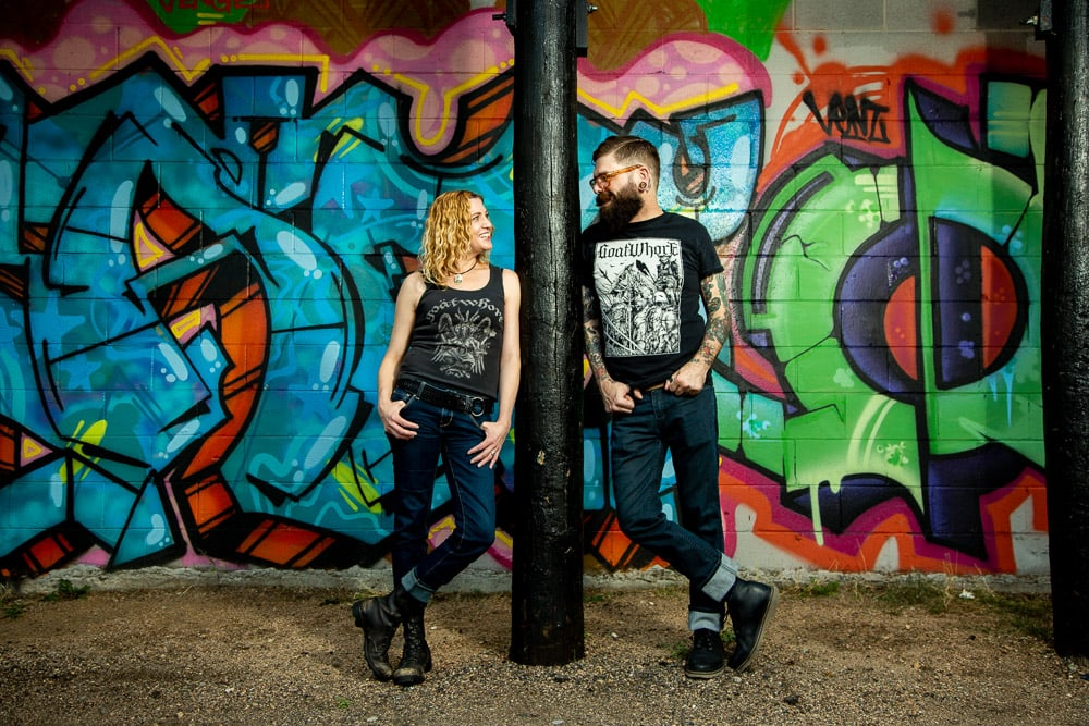 A couple leans against a post in front of a wall of graffiti for thier urban Denver engagement photos.