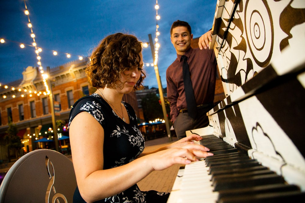 A girl playing the piano under the lights during her old town Fort Collins engagement photo session.